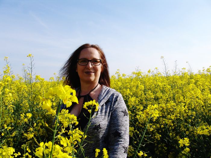 Smiling woman amidst yellow flowering plants against sky