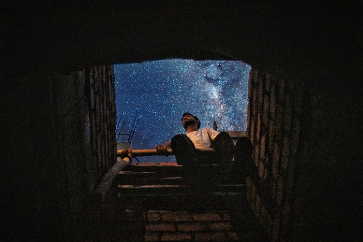 Young woman sitting on staircase at night