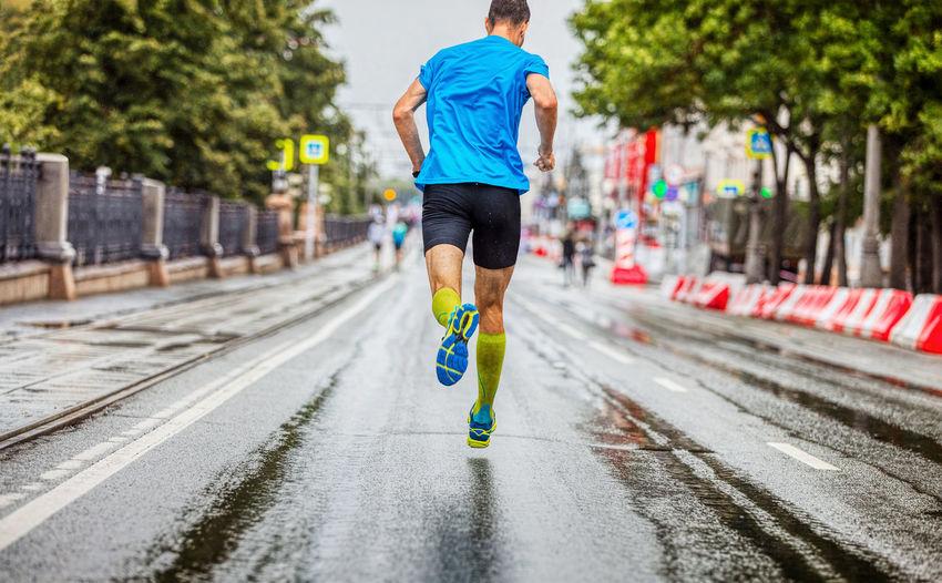 Back man athlete running marathon down street in rainy weather
