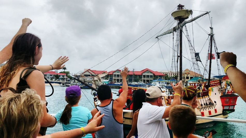 Cayman Islands Grand Cayman Grand Cayman Island Waving Waving Goodbye Tender Pirate Ship Water Ocean People Boat Fine Art Photography Group Group Of People Leaving Bye Sky Boat Ride Boats And Water Boat Life Boat Trip Group Photo Let's Go. Together.