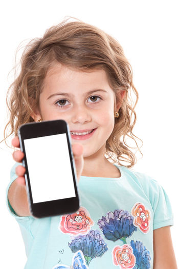 Young girl using smart phone. All on white background. Cell Phone  Child Childhood Copy Space Curly Hair Girl Girlhood Isolated On White Isolated White Background Kid Mobile Phone One Person Smart Phone Studio Shot Text Message Text Messaging Text Space White Background Young Girl