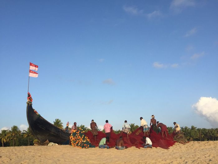 Fishermen Working At Beach Against Blue Sky