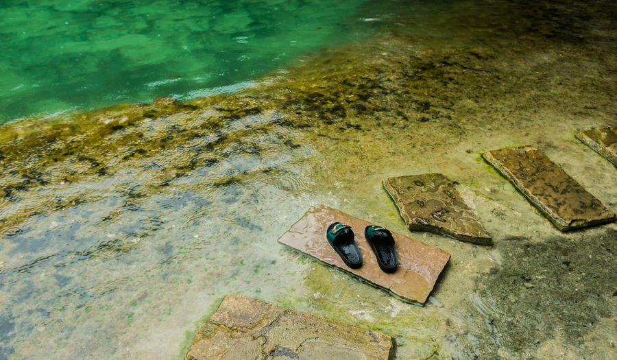 High Angle View Of Slippers On Stepping Stones At Lakeshore
