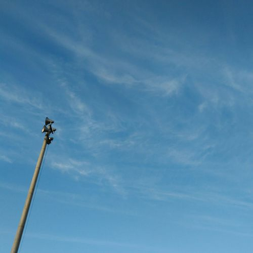 Low angle view of megaphones on pole against sky