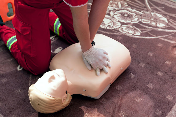 Midsection of paramedic performing cpr on dummy