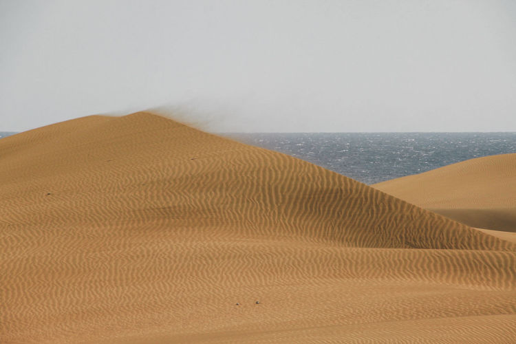 Sand dunes by sea against sky at grand canary
