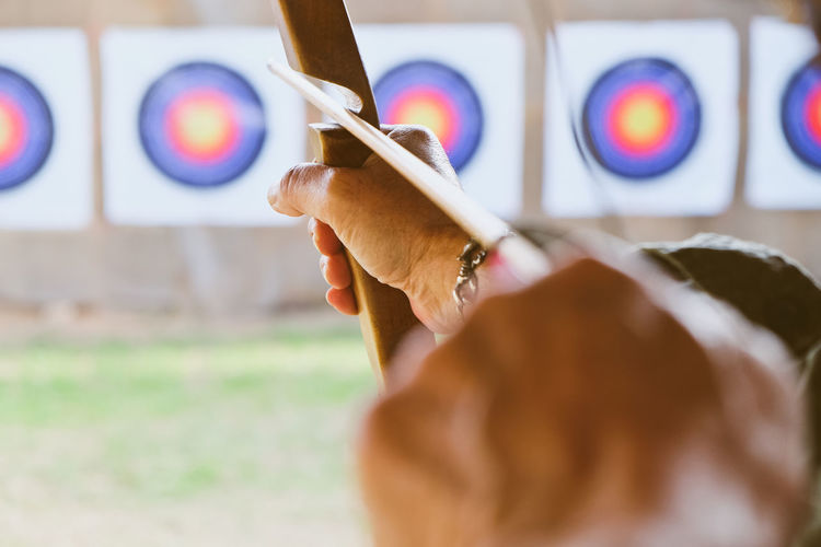 Archer holds his bow aiming at a target Arrow Bow Archer Archery Archery Bows Archery Competition Archery Target Close-up Human Hand One Person People Sport Sports Photography