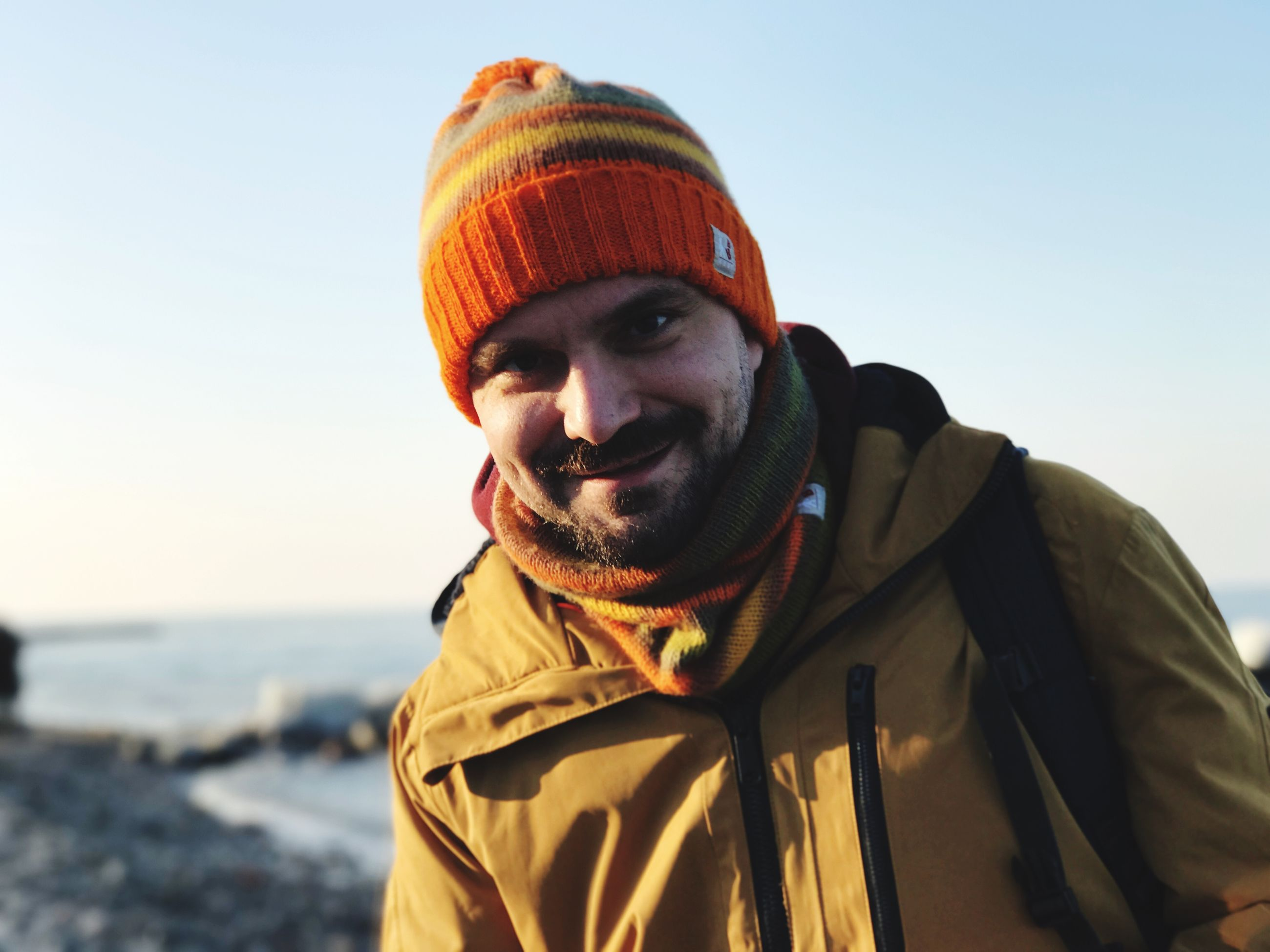 clothing, portrait, smiling, one person, looking at camera, warm clothing, winter, leisure activity, hat, real people, men, lifestyles, sky, knit hat, headshot, happiness, facial hair, nature, outdoors, scarf