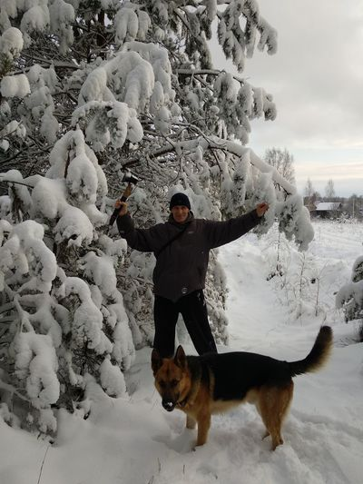 Portrait of smiling man with axe standing by dog and trees on snow during winter