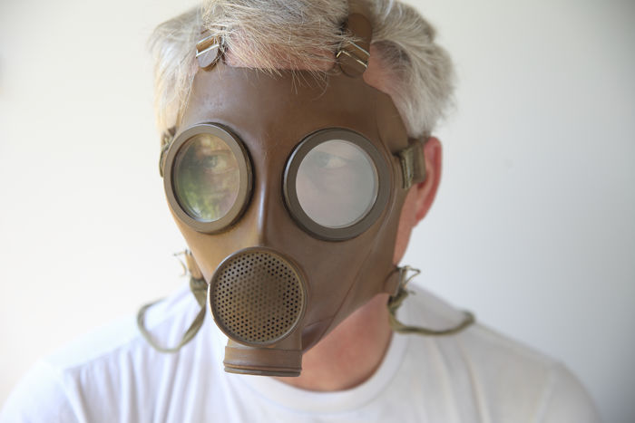 Old gas mask worn by senior man Biological Hazard Brown Chemical Warfare Disturbing Equipment Eyes Fearful Front View Gas Mask Headshot Man Military Old Poison Pollutants Protection Senior Straps Toxic Vintage WWII