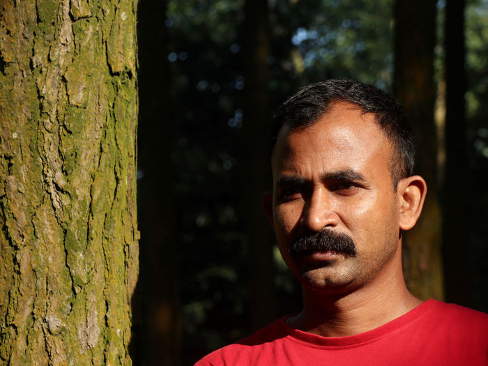 Close-up portrait of man against tree trunk