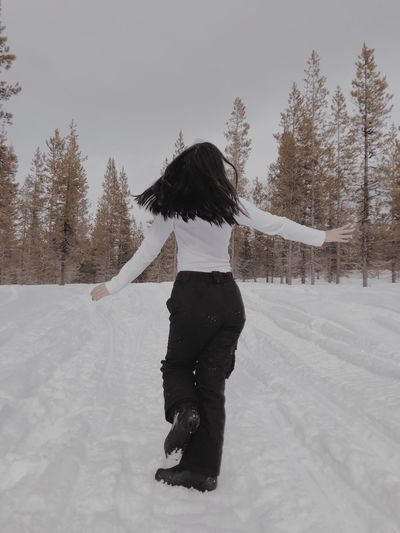 Rear view of young woman standing on snow covered land