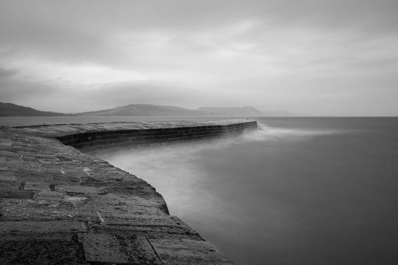 Long exposure of lyme regis pier in dorset in black and white