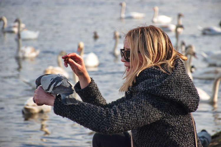 Pigeon perching on woman hand at lakeshore