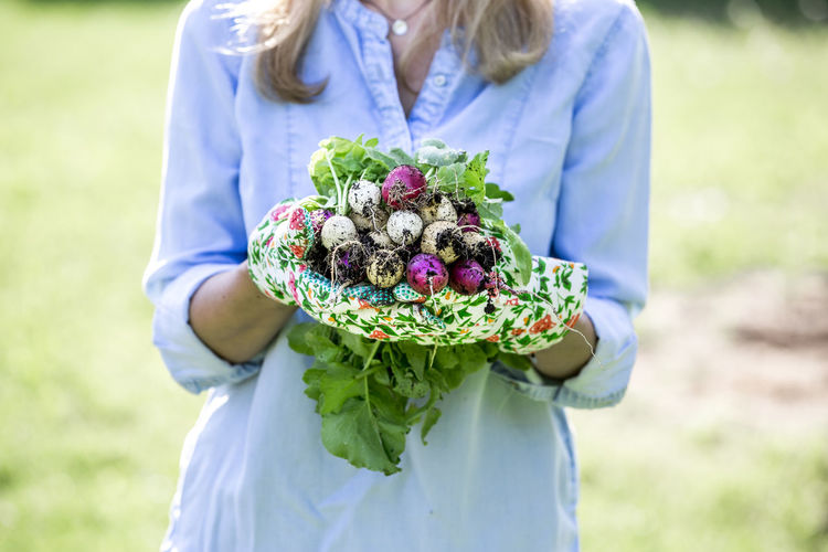 Mid adult woman holding radishes at farm