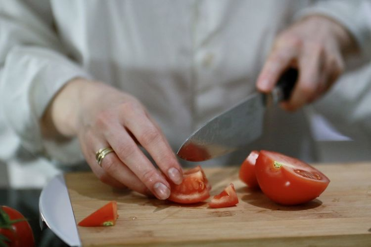 Midsection of person preparing food on cutting board