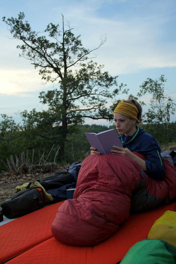 young caucasian female reading book while outdoor camping Backpacking Camping Hiking Nature Reading Travel Trekking Woman Activity Book Casual Clothing Caucasian Cloud - Sky Communication Connection Education Female Girl Hikingadventures Hobby Leisure Activity Lifestyles Nature One Person Outdoors Paper People person Plant Real People Relaxation Sitting Sky Technology Tent Three Quarter Length Tree Vacation Wireless Technology