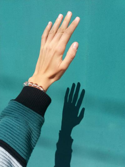 Close-up of human hand against turquoise wall