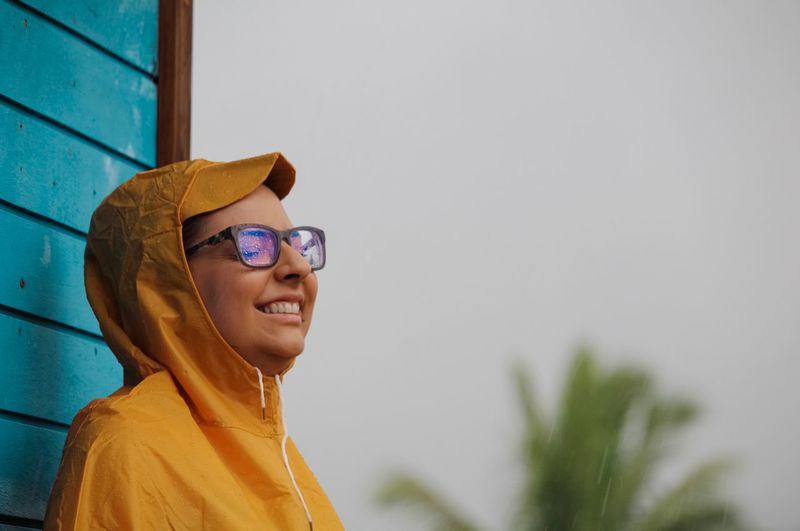 Side view of smiling young woman wearing sunglasses and raincoat during rainy season