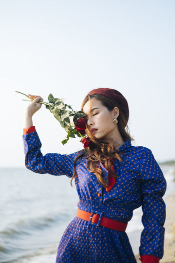 Young woman holding rose standing at beach against sky