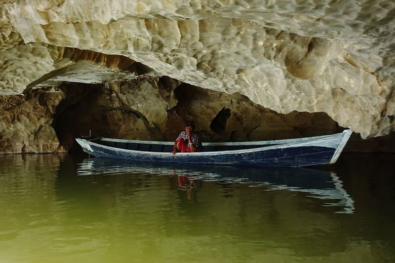 Man in boat on rive by rock formation