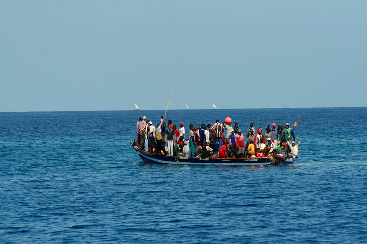 Zanzibar, Tanzania - February 16, 2008: Residents of Tanzania moved by boat between the islands, near Zanzibar, a large group of Africans standing in a heavily overburdened boat in the Indian Ocean, February 16, 2008. Zanzibar Africa Ocean Stone Town Stone Town Zanzibar Crossing Ocean Boat Floating In Ocean Barely Seaworthy Boat Boatloads; Overloaded Boat; Overloaded Crowded Boat Tanzania Outdoors Horizon Over Water Large Group Of People Clear Sky Crowd Horizon Nautical Vessel Sea Water Sky Group Of People