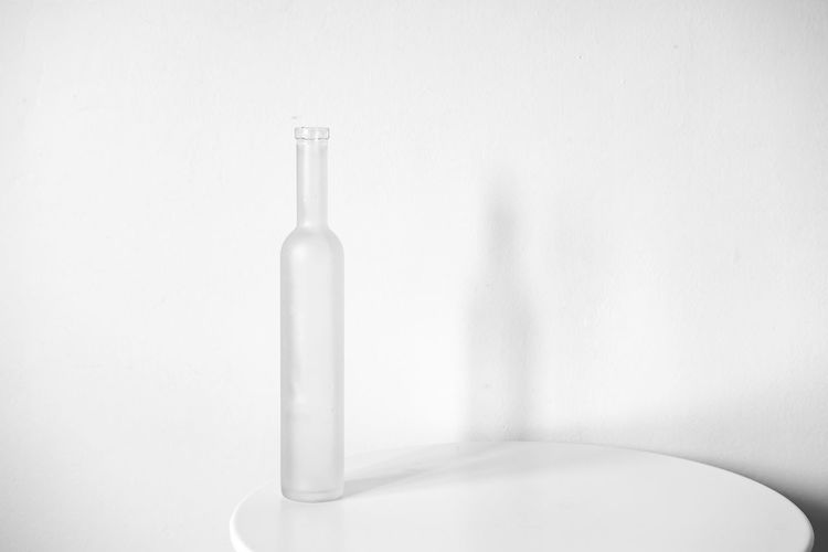 Close-up of glass bottle on table against white background