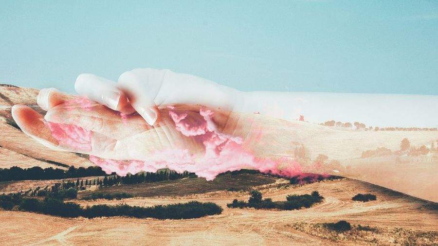 Collage of hand with pink clouds over tuscany land