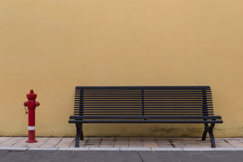 Empty bench against wall in park