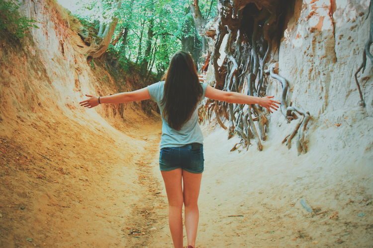 Rear view of woman with arms outstretched standing amidst rock formation