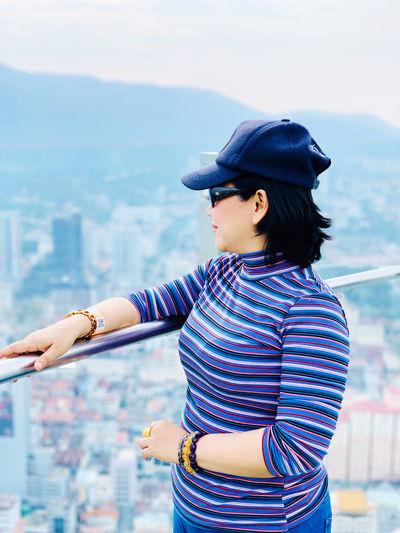 Woman wearing cap standing by railing