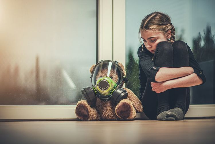 Girl with teddy bear wearing mask sitting against window