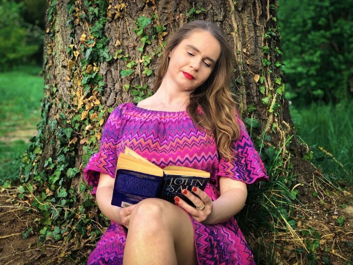 Woman in pink dress leaning against a tree while reading a book