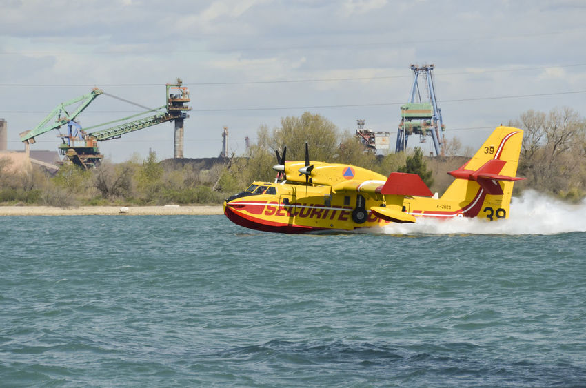 Canadair, water bomber plane in training in the harbor Firefighter Plane Aircraft Airplane Canadair Cloud - Sky Day Mode Of Transportation Motion Outdoors Sea Sky Transportation Water Water Bomber Waterfront