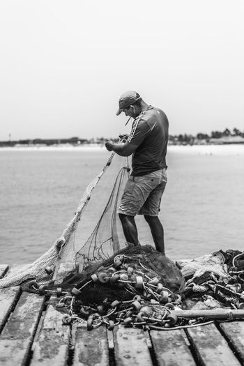 Fisherman fixing his nets Adult Fisherman Fishing Fishing Net Full Length Holding One Person Outdoors People Real People Sea Standing Water