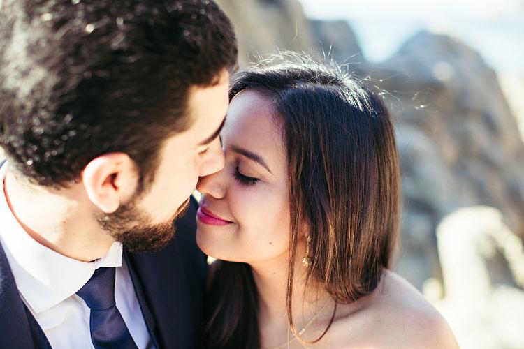 Close-Up Of Newlywed Couple Romancing At Beach