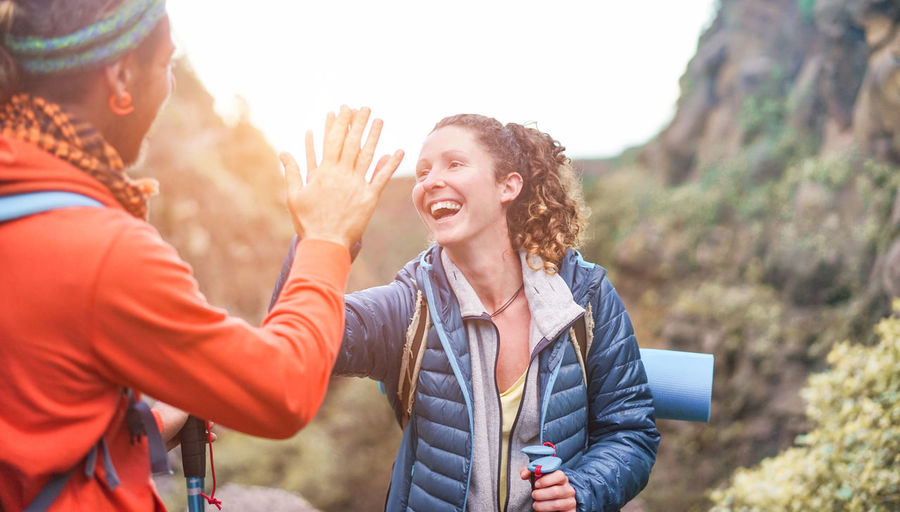 Smiling woman giving high-five to friend while standing against mountains