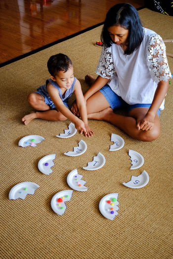 High angle view of mother and son playing with toys at home