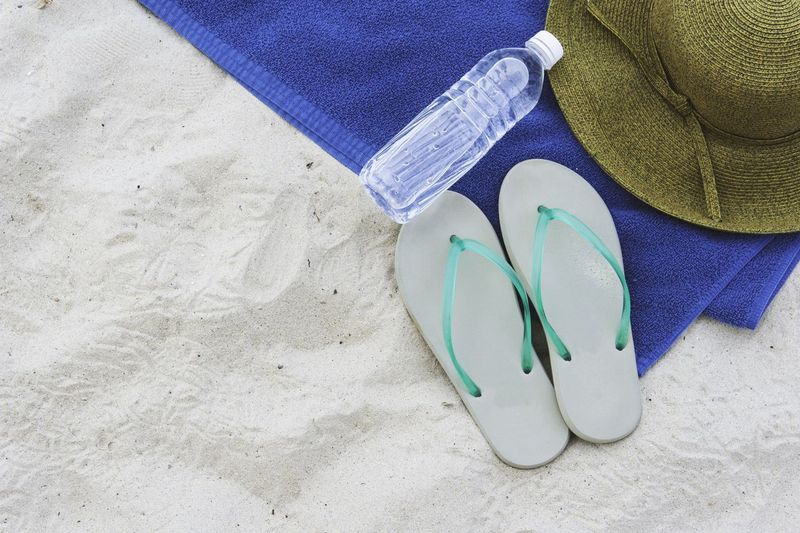High angle view of flip-flops and bottle at sandy beach