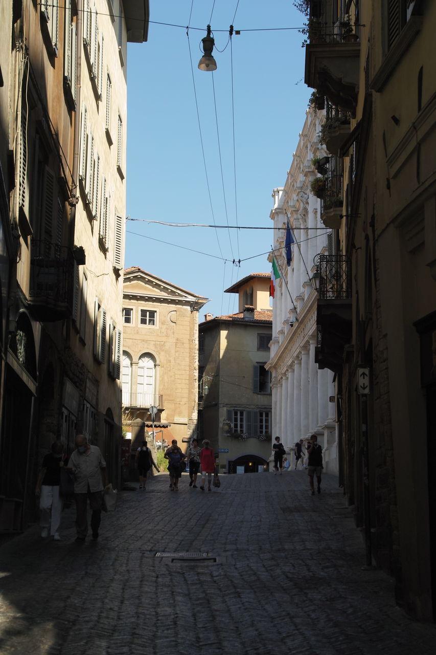 PEOPLE WALKING ON STREET AMIDST BUILDINGS AGAINST SKY