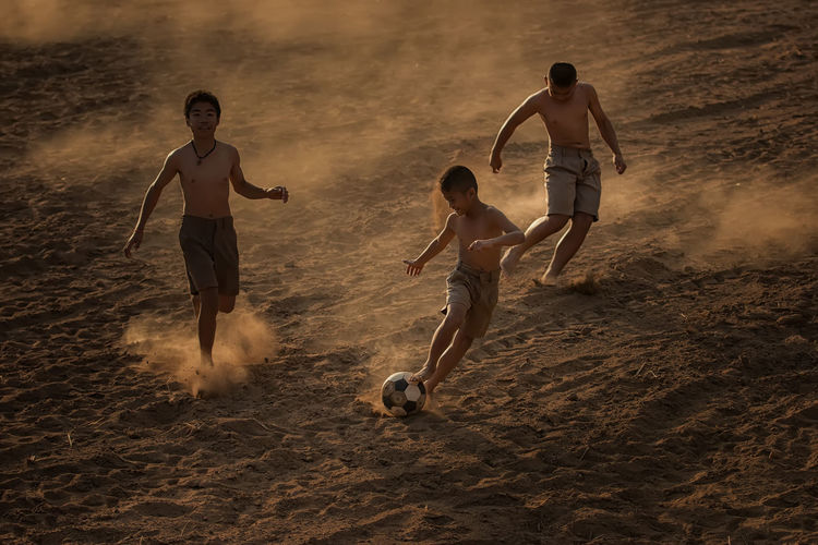 Children playing football at the countryside. Ball Boys Child Childhood Full Length Group Of People Land Leisure Activity Lifestyles Males  Men Motion Nature Playing Real People Running Shirtless Soccer Ball Sport Sunset Teenage Boys