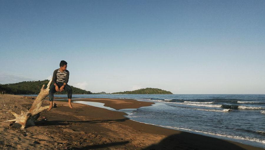 Man Sitting On Driftwood At Beach Against Sky