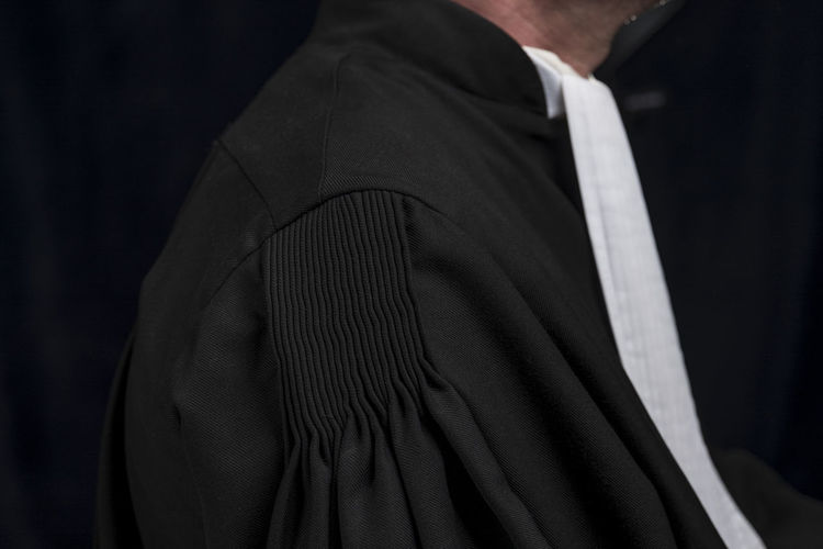 Side view of lawyer standing against black background