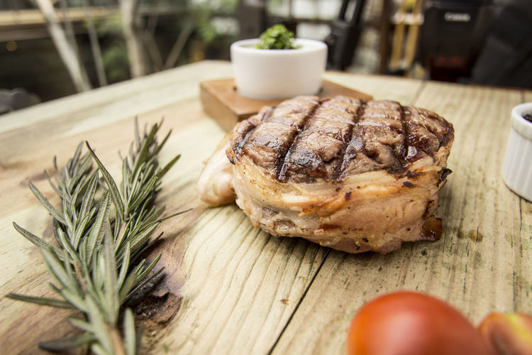 Close-up of grilled tuna with rosemary on wooden table