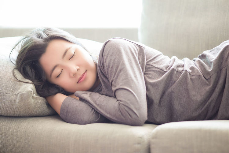 Young Woman Sleeping On Sofa At Home
