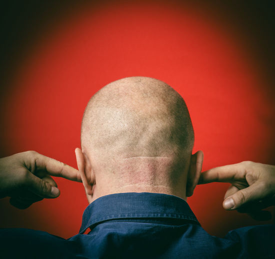 Rear View Of Mature Man With Fingers In Ears Against Red Background