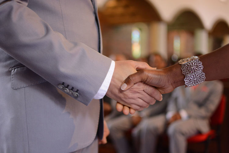 Midsection of wedding couple holding hands in church