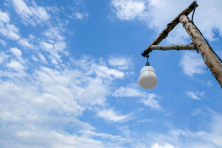 Low angle view of lighting equipment hanging against sky