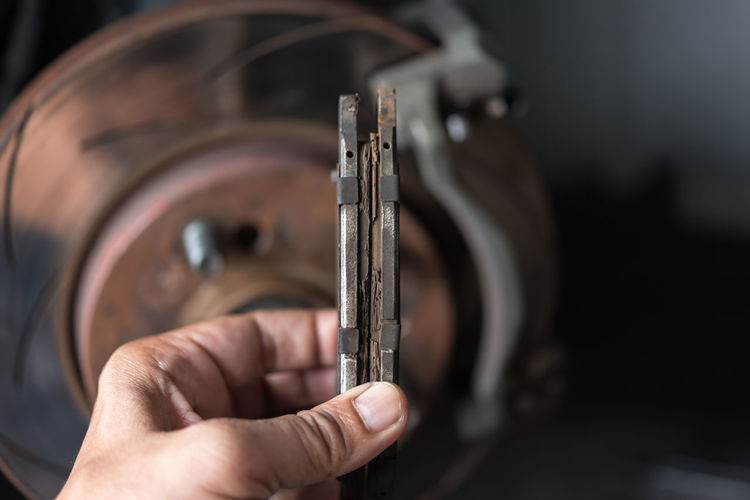 Cropped hand of man holding old machine part
