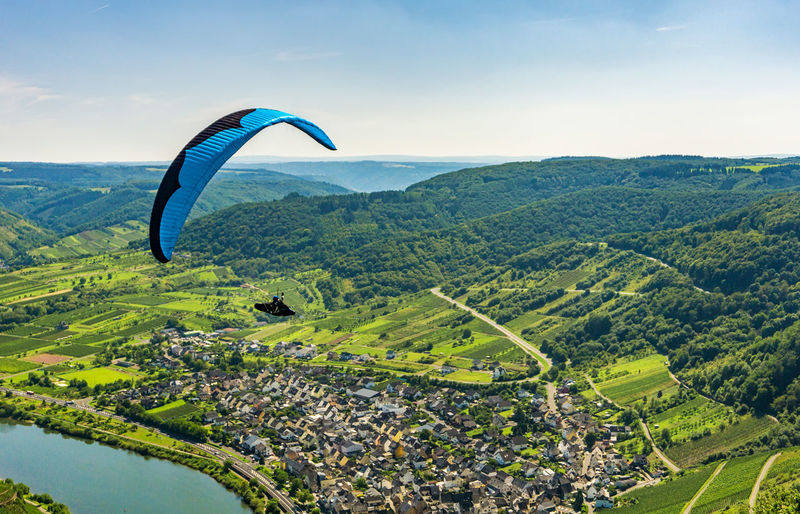 Scenic view of parachute over landscape against sky